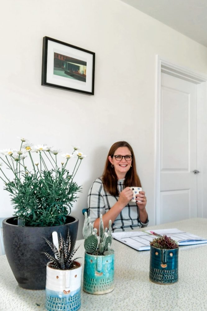 Lynda Pepper - smiling. Sitting at a table with a cup of tea