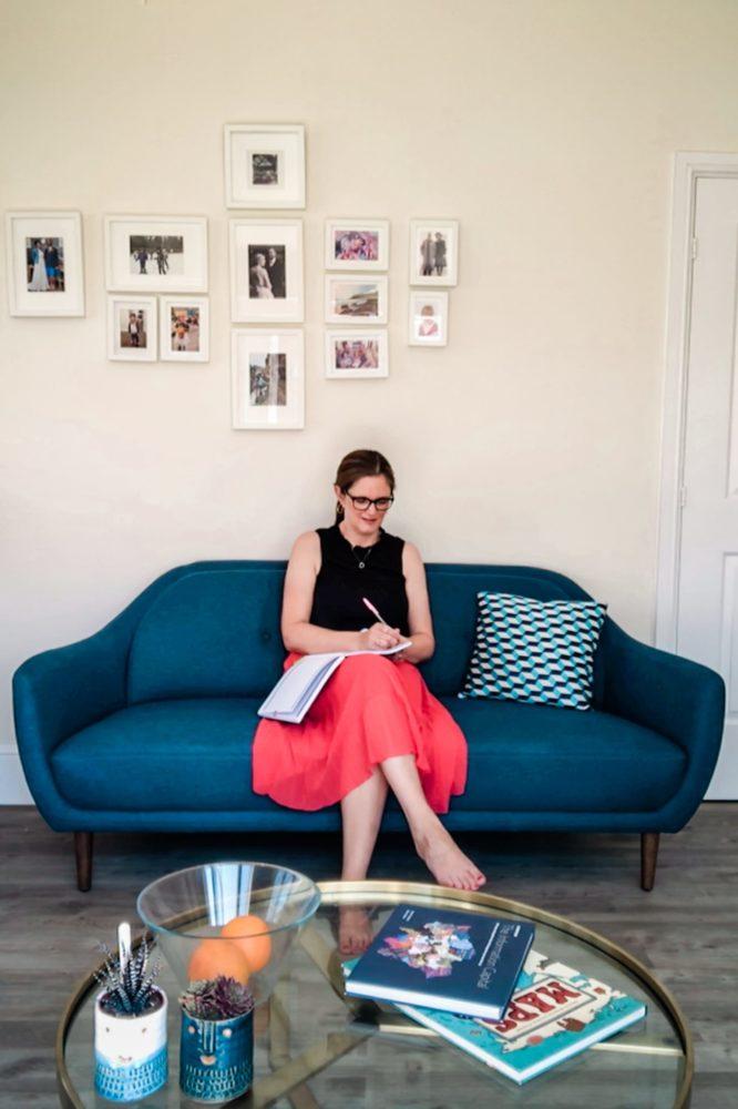 Lynda Pepper sitting on a sofa writing in notebook