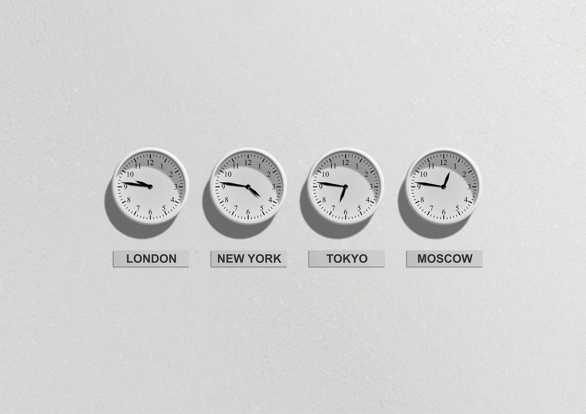 Four clocks on a wall telling the time in different cities